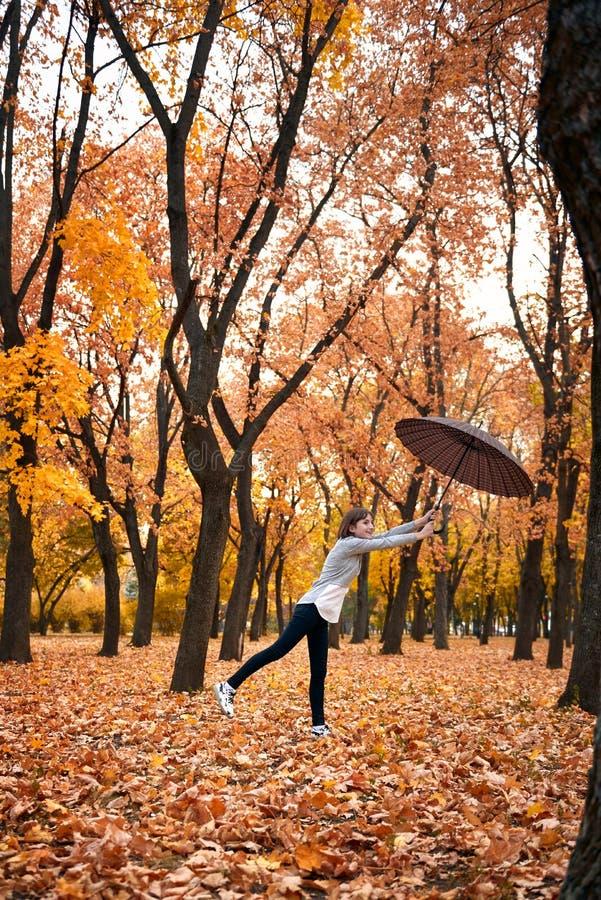 A menina adolescente está levantando com o guarda-chuva no parque do outono Paisagem bonita no outono fotografia de stock