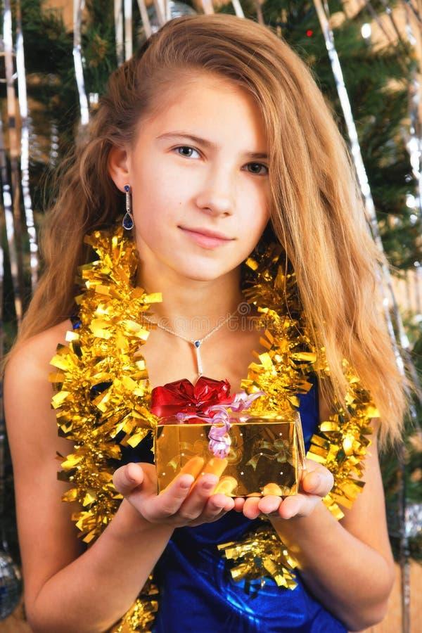 A menina adolescente feliz bonita guarda antes dse um presente do Natal imagem de stock royalty free