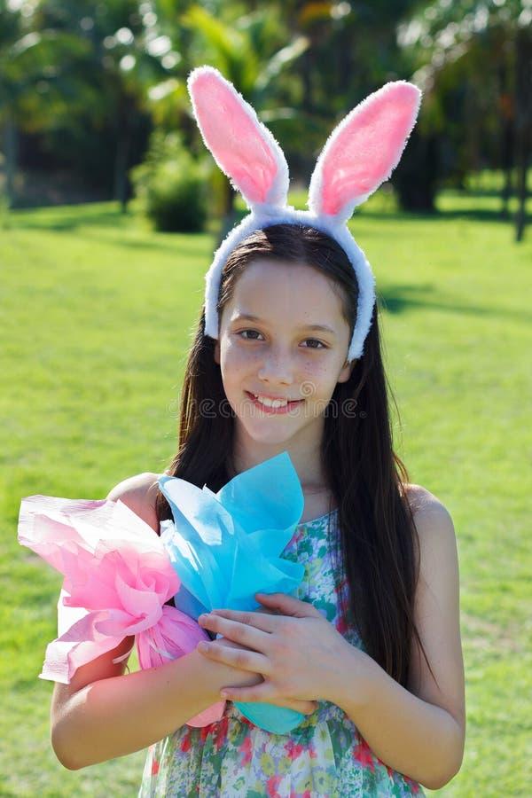 Menina adolescente feliz de sorriso com orelhas de coelho e chocolate da Páscoa por exemplo imagens de stock royalty free