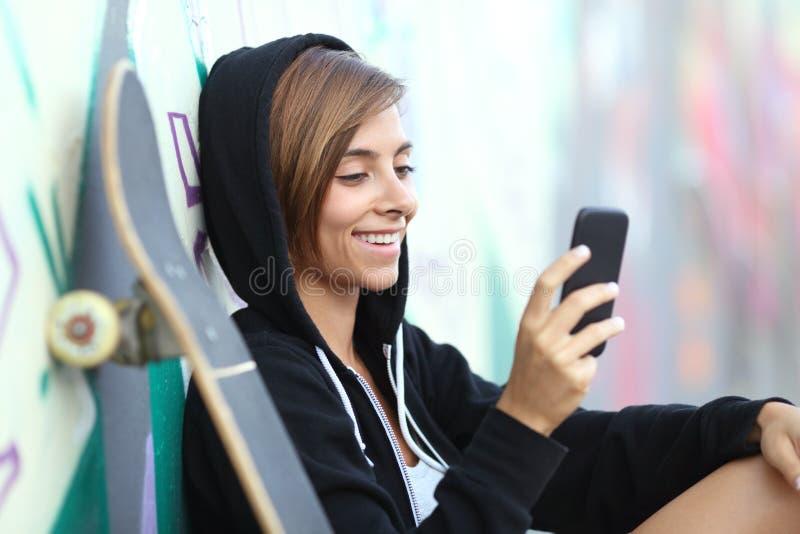 Menina adolescente feliz do skater novo que usa um telefone esperto fotografia de stock royalty free
