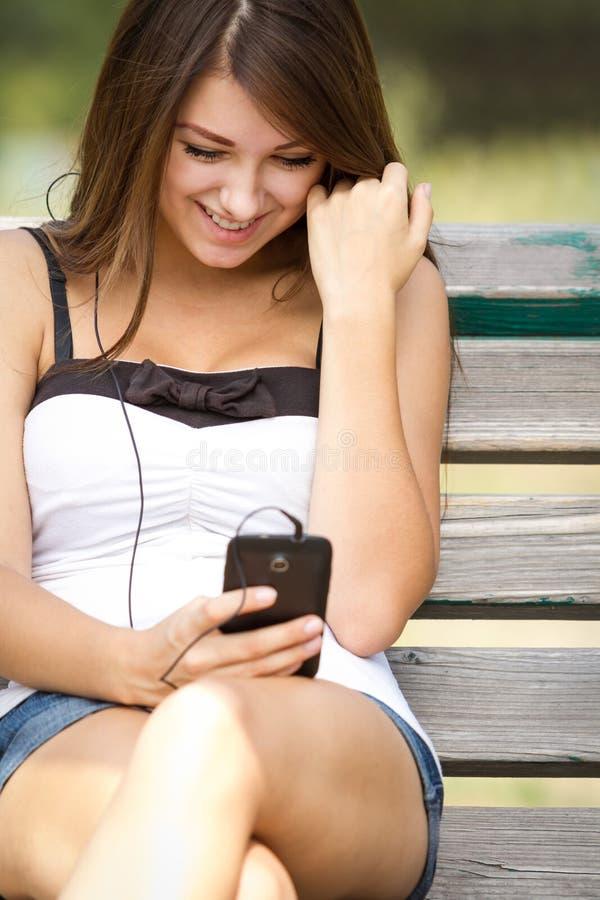 Menina adolescente feliz que escuta a música no smartphone fotografia de stock royalty free