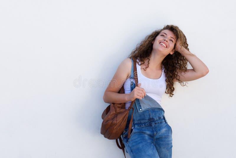 Menina adolescente feliz que está com mão na cabeça e no saco imagem de stock royalty free