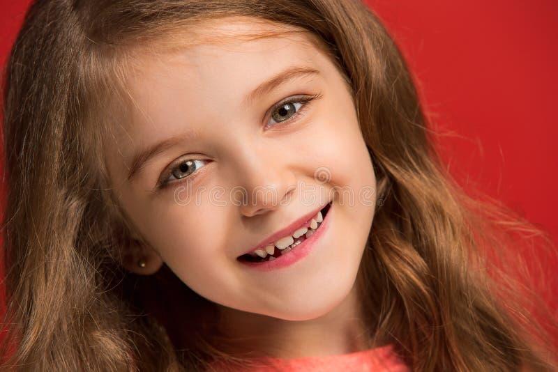 A menina adolescente feliz que está e que sorri contra o fundo vermelho imagens de stock