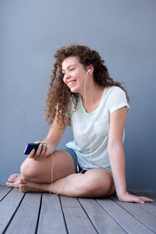 Menina adolescente feliz que senta-se no assoalho que escuta a música fotos de stock royalty free