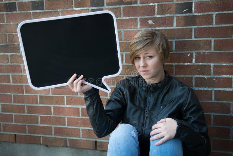 A menina adolescente guarda o sinal preto foto de stock royalty free
