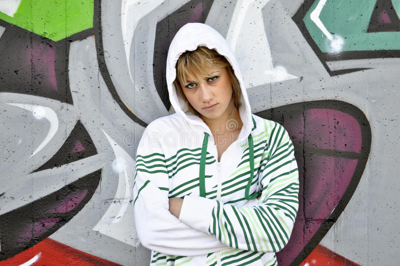 A menina adolescente inclinou-se de encontro à parede dos grafittis fotos de stock