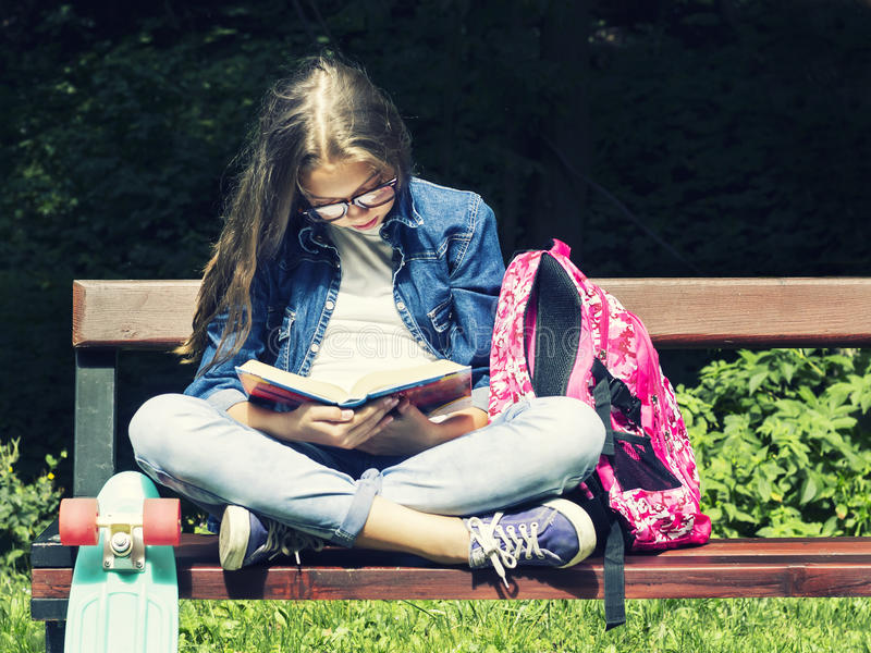 Menina adolescente loura bonita na camisa das calças de brim que lê um livro no banco com uma trouxa e um skate no parque imagem de stock