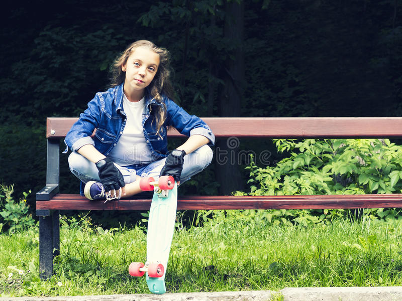 Menina adolescente loura bonita na camisa das calças de brim, sentando-se no banco com trouxa e skate no parque imagens de stock