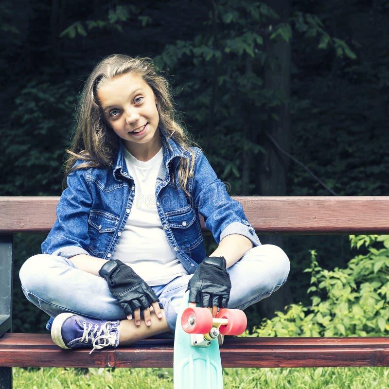 Menina adolescente loura bonita na camisa das calças de brim, sentando-se no banco com trouxa e skate no parque fotografia de stock royalty free