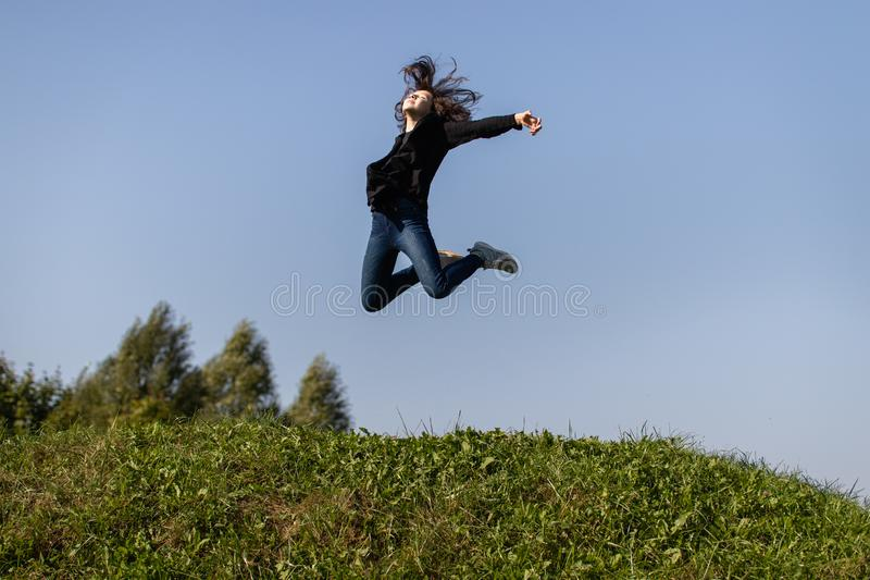 Menina adolescente magro que salta altamente sobre a grama verde contra o céu imagem de stock royalty free