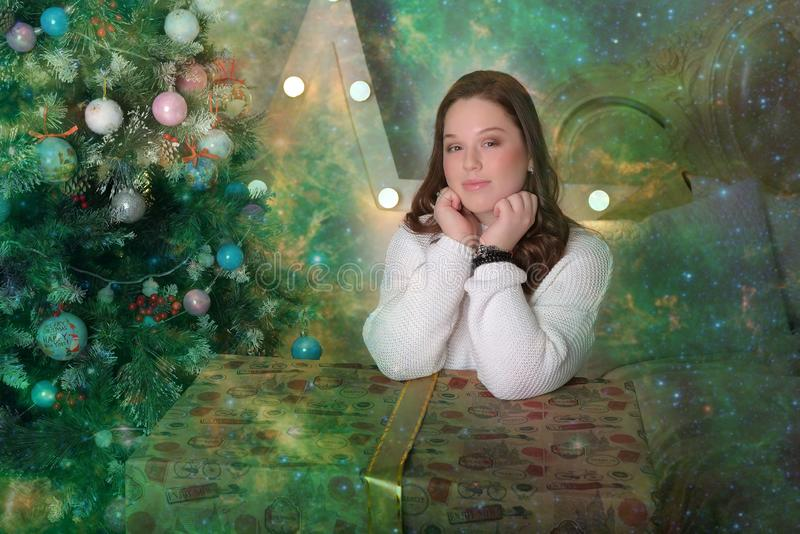 Menina adolescente moreno bonita em uma camiseta branca com uma caixa enorme com um presente pela árvore de Natal fotos de stock