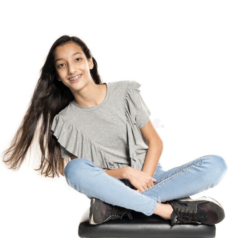A menina adolescente moreno senta-se no tamborete de piano fotos de stock royalty free
