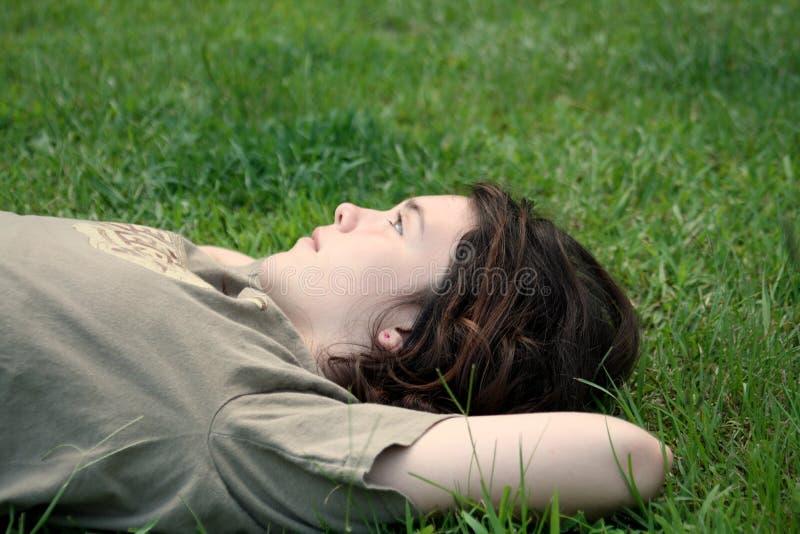 Menina adolescente na grama que daydreaming imagens de stock