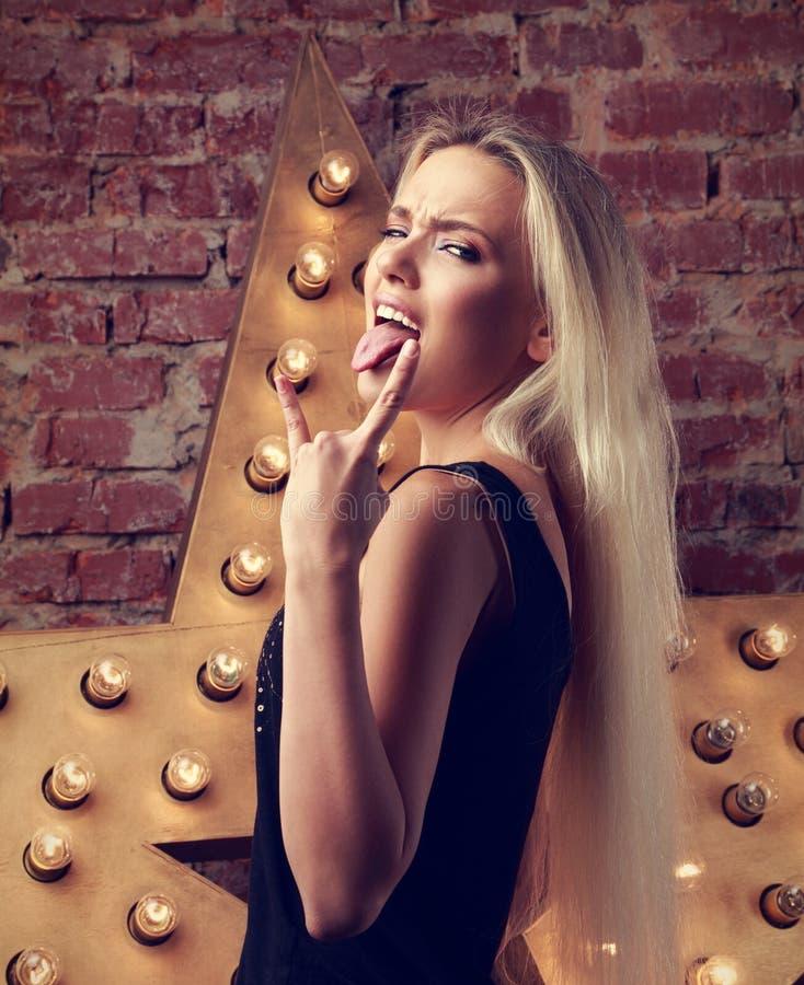 Menina adolescente na moda loura do divertimento emocional bonito que mostra o tongu imagem de stock