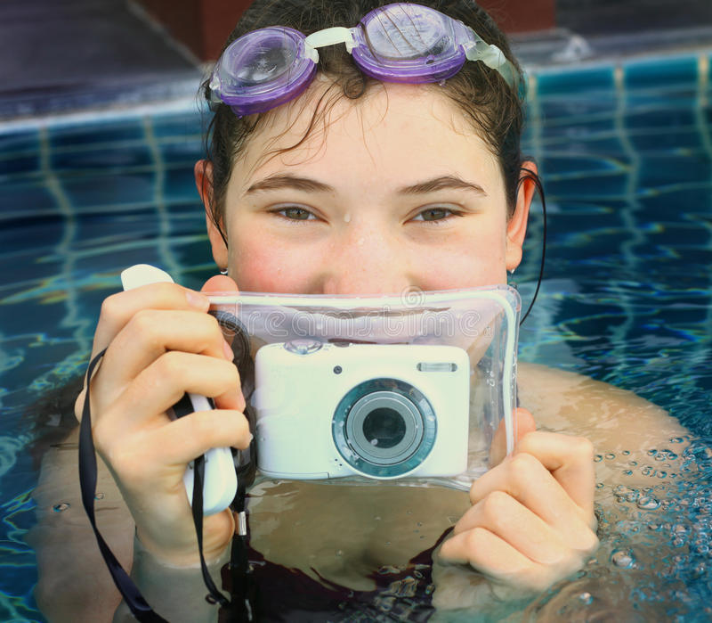 Menina adolescente na piscina com câmera do underwter fotografia de stock royalty free
