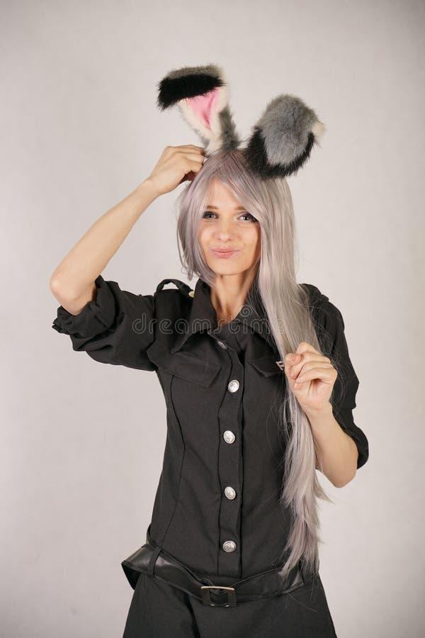 A menina adolescente no vestido do carnaval do preto do FBI com as orelhas de coelho grandes da pele ama cosplay e está no fundo  imagens de stock royalty free