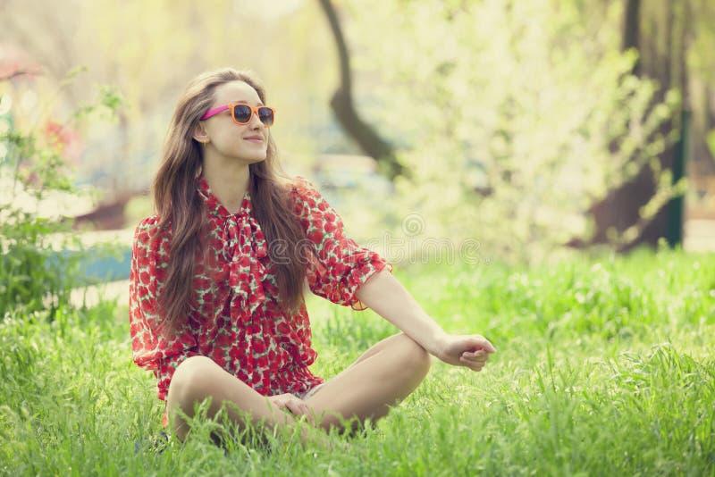 Menina adolescente nos vidros no parque. imagem de stock royalty free