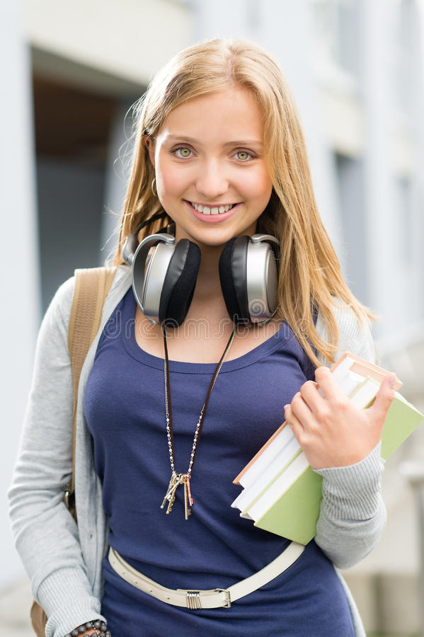 Menina adolescente nova do estudante com auscultadores dos livros imagem de stock royalty free