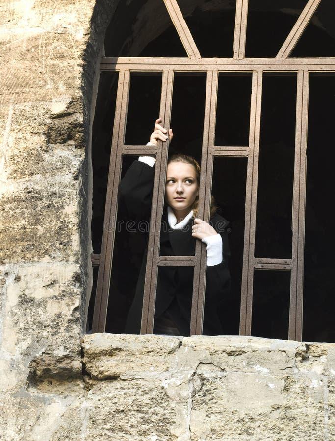 A menina adolescente olha fora do indicador da cadeia fotografia de stock