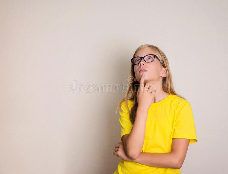 Menina adolescente pensativa nos monóculos que olham acima Thi consideravelmente ocasional imagens de stock