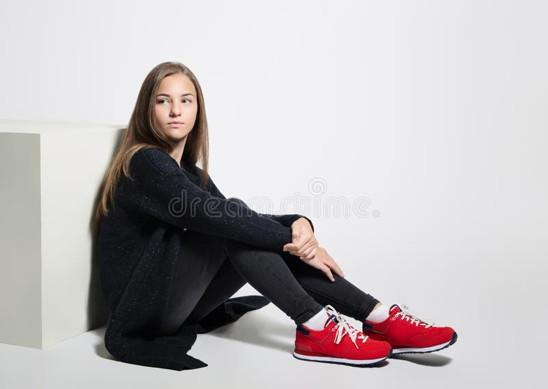 Menina adolescente pensativa que levanta o assento no assoalho no estúdio Roupa preta, branco vermelho das sapatas fotografia de stock