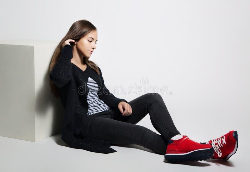 Menina adolescente pensativa que levanta o assento no assoalho no est?dio Roupa preta, branco vermelho das sapatas imagem de stock royalty free