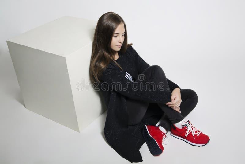 Menina adolescente pensativa que levanta o assento no assoalho no est?dio Roupa preta, branco vermelho das sapatas imagens de stock