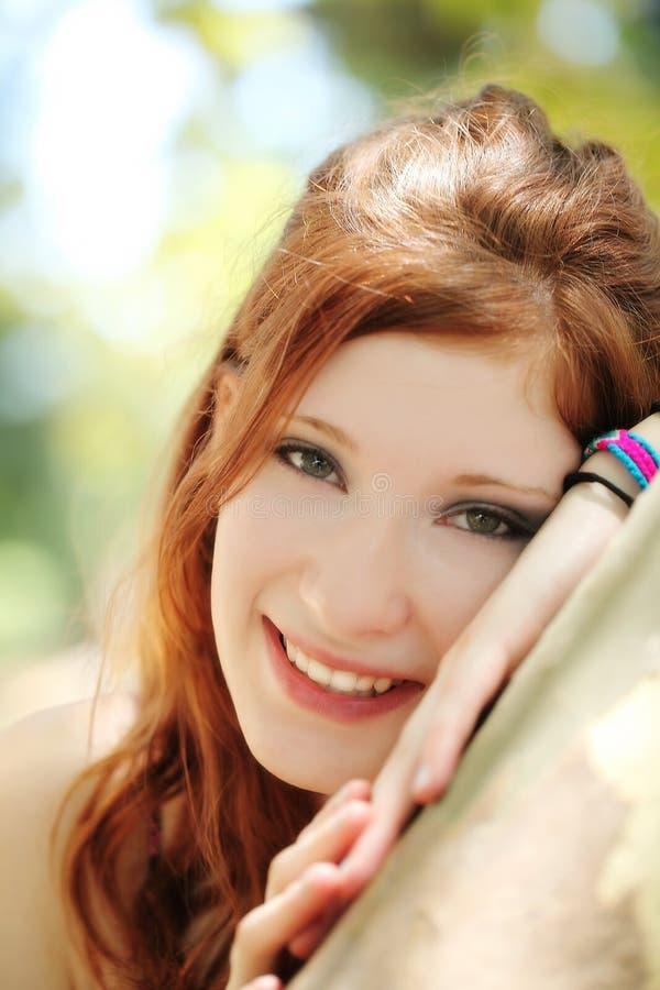 Menina adolescente principal vermelha de sorriso do retrato exterior imagens de stock royalty free