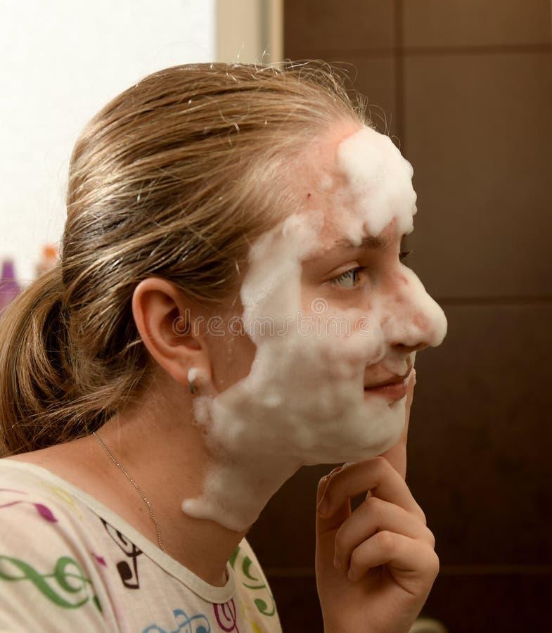 Menina adolescente que aplica uma máscara da bolha imagem de stock