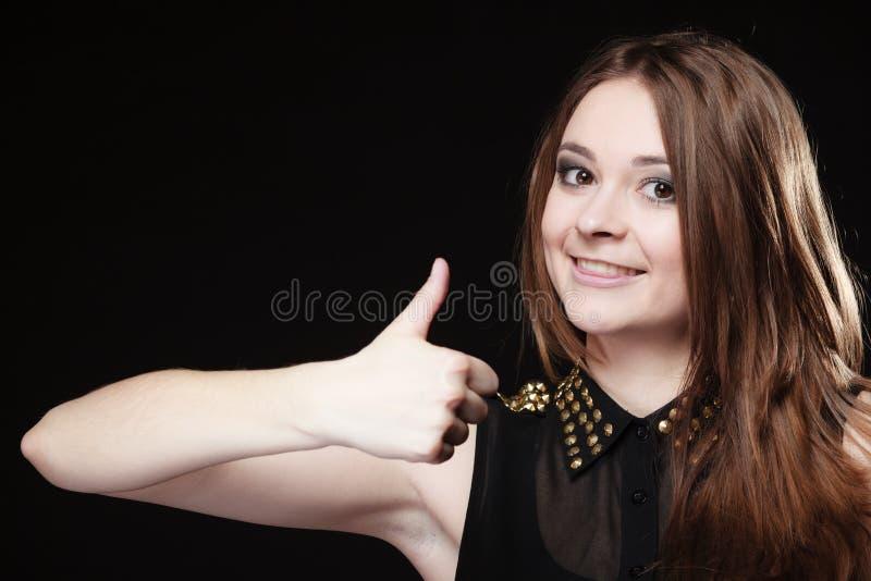 A menina adolescente que dá os polegares levanta o sinal no preto fotos de stock