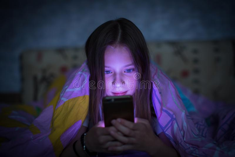 Menina adolescente que encontra-se na cama e que olha a tela de incandescência do smartphone foto de stock royalty free