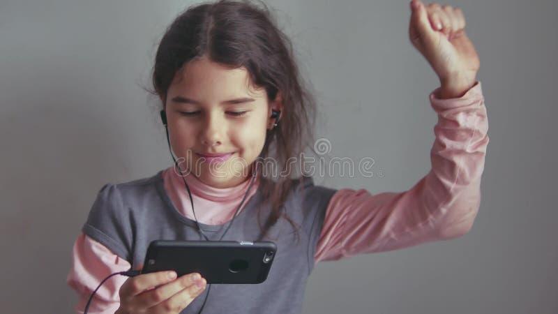 Menina adolescente que escuta a música em fones de ouvido e que dança em um smartphone foto de stock royalty free
