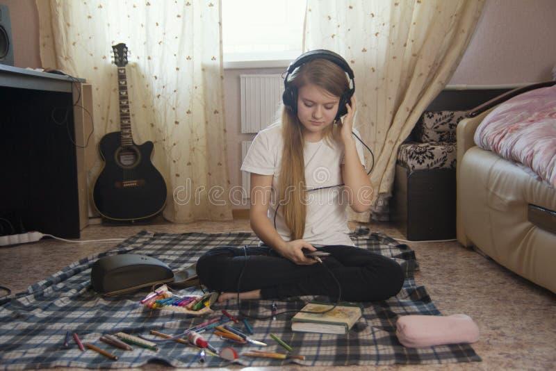 Menina adolescente que escuta a música nos fones de ouvido usando o smartphone que senta-se no assoalho em casa imagens de stock