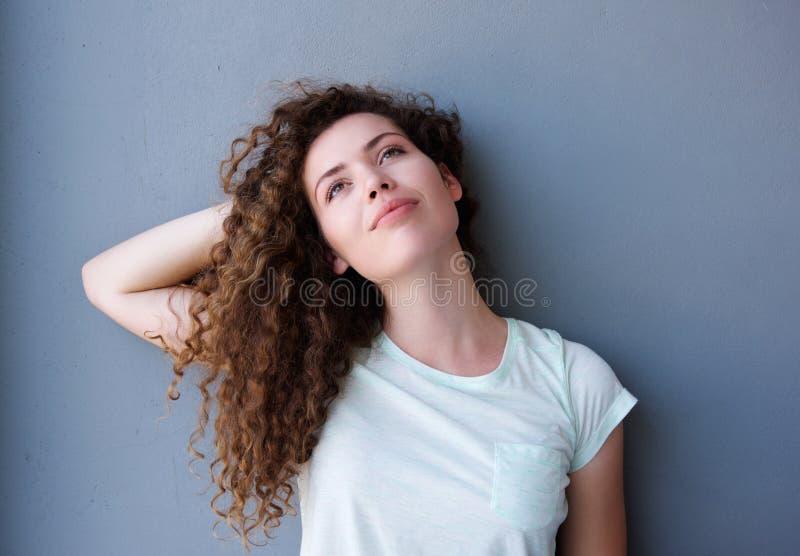 Menina adolescente que está com mão atrás do pensamento principal imagens de stock royalty free