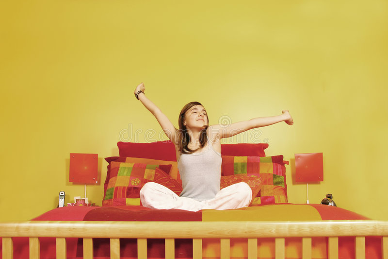 Menina adolescente que estica na cama fotografia de stock royalty free