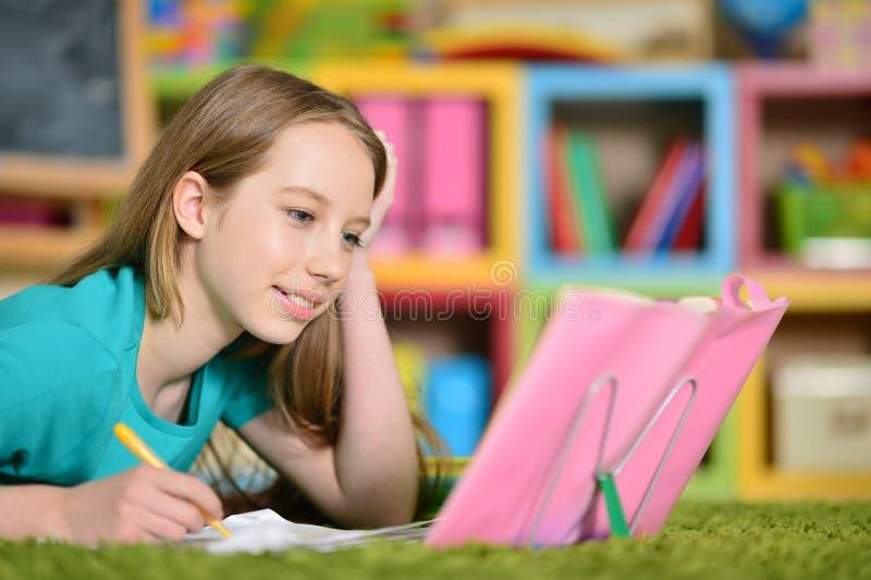 Menina adolescente que faz trabalhos de casa fotografia de stock