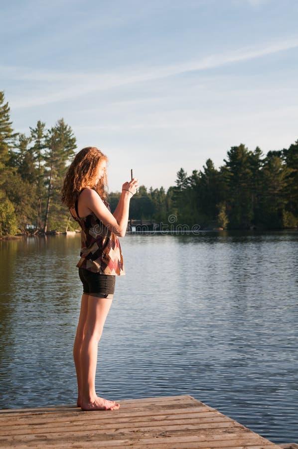 Menina adolescente que fotografa com seu telefone imagem de stock royalty free