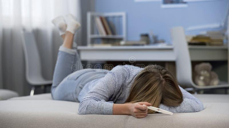 Menina adolescente que grita devido à gravidez adiantada, sentindo bebê desesperado, indesejável fotos de stock