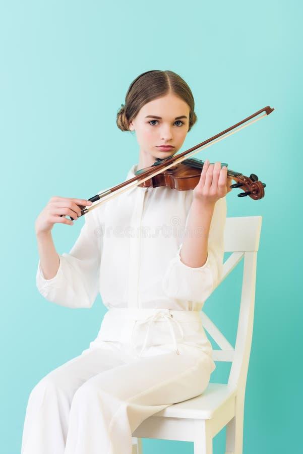 menina adolescente que joga o violino e que senta-se na cadeira fotos de stock royalty free