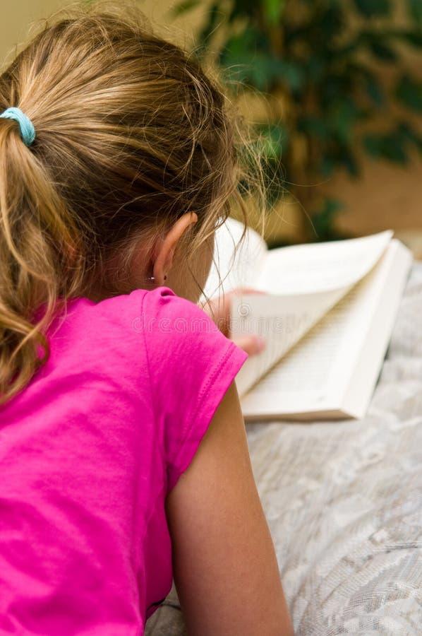 Menina adolescente que lê um livro na cama imagem de stock