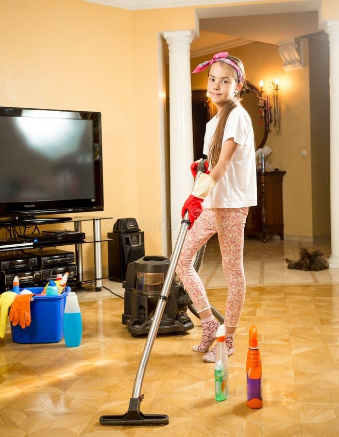 Menina adolescente que limpa o assoalho na sala com o aspirador de p30 fotos de stock