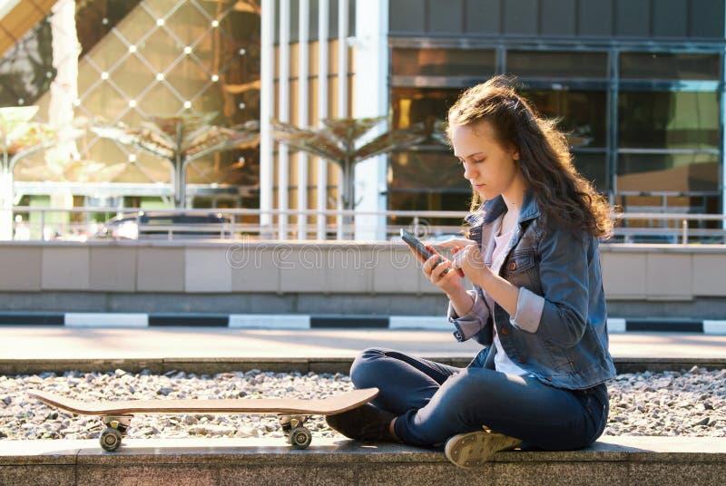 Menina adolescente que manda um telefone celular sentar-se em um assoalho em uma cidade imagem de stock royalty free