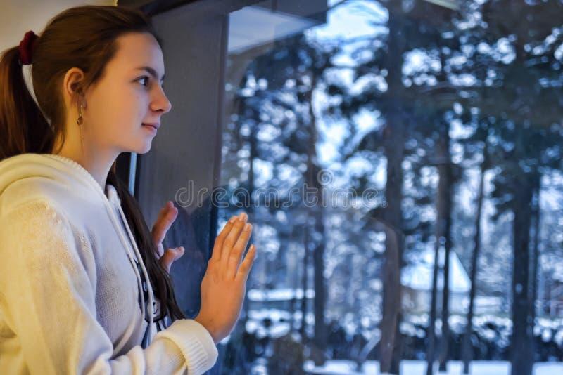 Menina adolescente que olha para fora a janela com uma paisagem do inverno fotos de stock