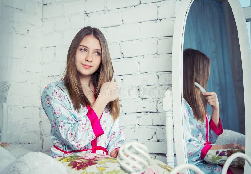 Menina adolescente que penteia seu cabelo imagem de stock