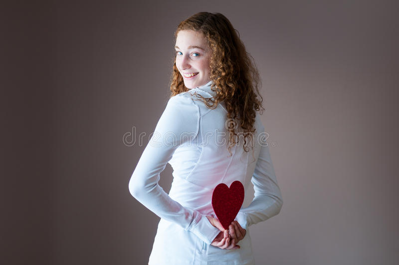 Menina adolescente que retém corações atrás dela imagens de stock royalty free