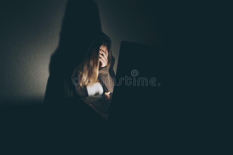 Menina adolescente que senta-se excessivamente no portátil do computador em casa é uma vítima de redes tiranizando em linha do so imagem de stock