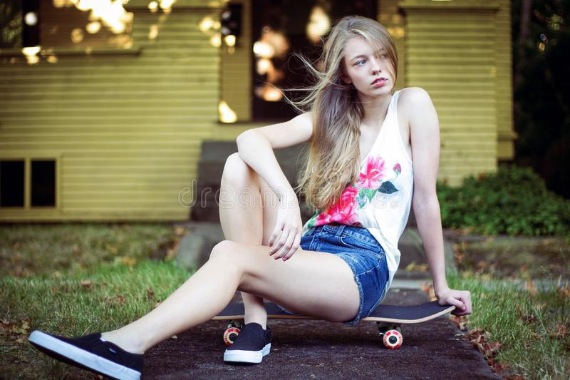 Menina adolescente que senta-se na placa do patim perto da casa foto de stock royalty free