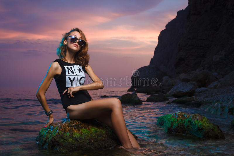 Menina adolescente que senta-se no tiro de pedra da forma no por do sol imagem de stock