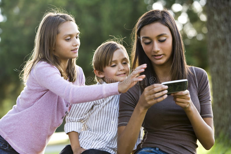 Menina adolescente que texting, relógio mais novo dos irmãos imagens de stock