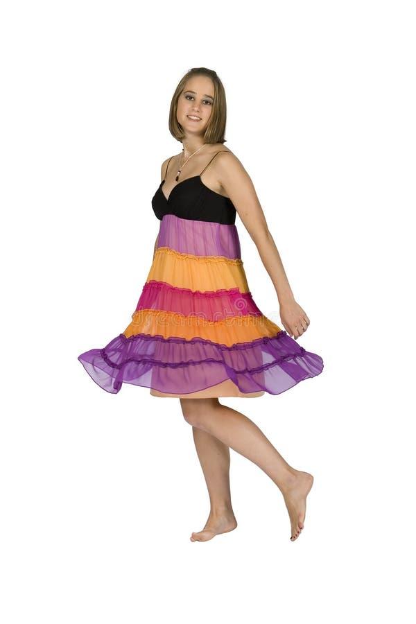 Menina adolescente que Twirling no vestido colorido - isolado fotografia de stock royalty free